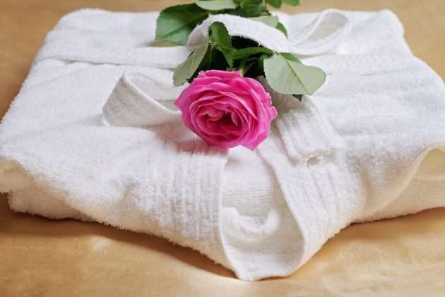 Stack of white  and soft hotel towels and bathrobe decorated with rose flower. Perfect white laundry. Spa, healthy lifestyle and relaxation concept.