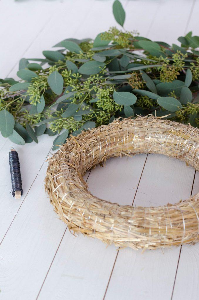 Strohrömer, Eukalyptus und Wickeldraht auf einem weißen Holztisch