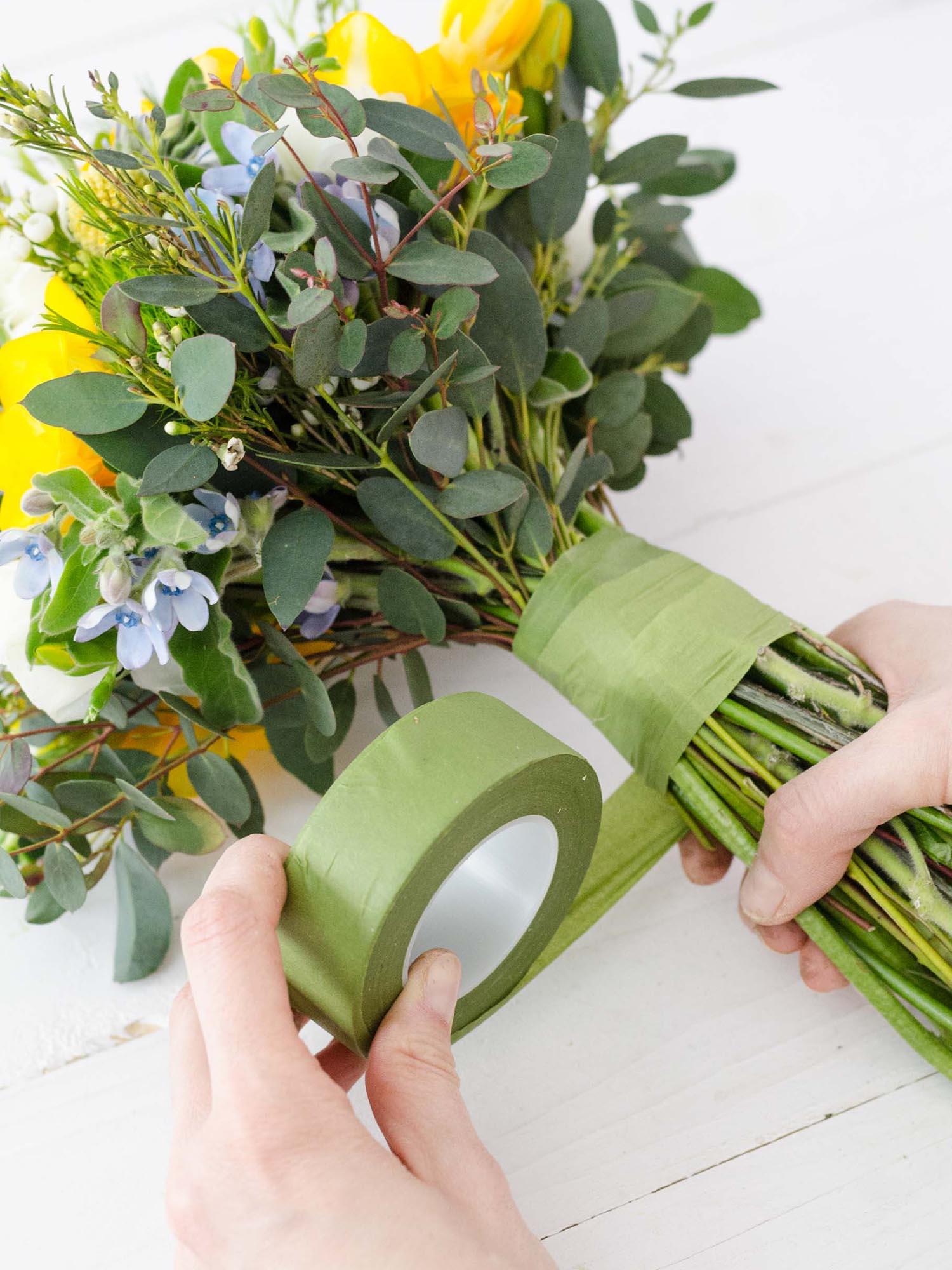 Blumenstrauß der mit Floristentape gebunden wird