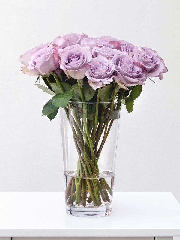 Blumen Glasvase Jasmin 25 cm hoch mit lila Rosen im Milieu gefüllt