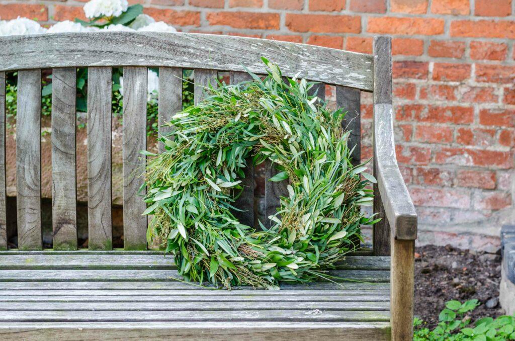 Greenery Kranz aus Olivenzweigen auf Holzbank