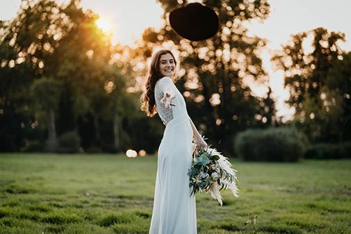 Braut auf Wiese mit Bohokleid und Bohostrauß und Hut