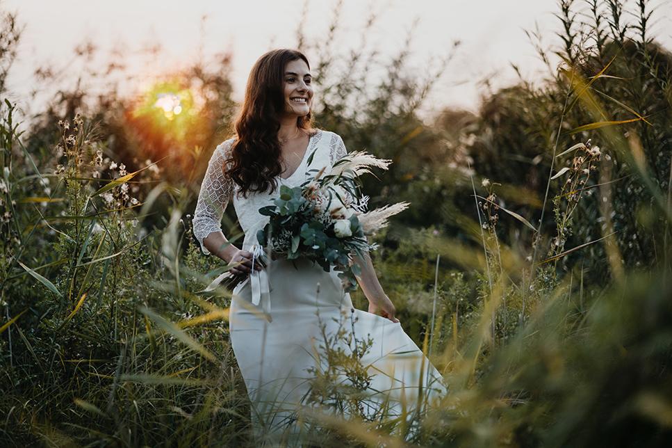 Braut auf Blumenwiese mit Boho-Brautstrauß