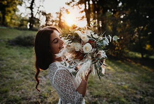 Braut mit Boho-Brautstrauß im Sonnenuntergang