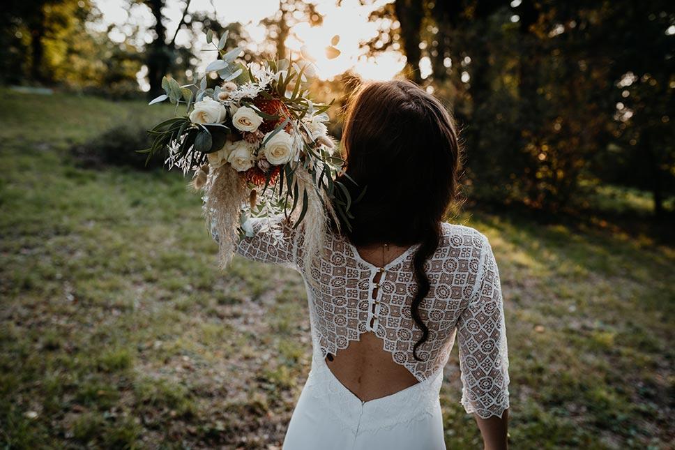 Braut im Boho-Brautkleid mit Brautstrauß aus Trockenblumen und Schnittblumen
