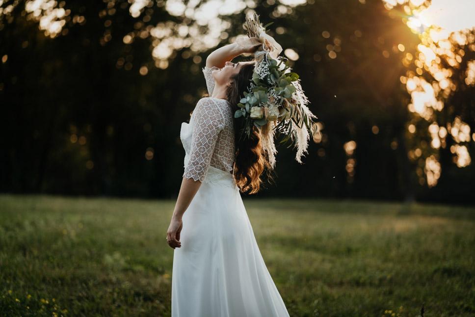 Braut auf Wiese im Boho Kleid mit Boho Brautstrauß