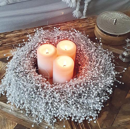 Weißer Flachskranz mit drei schlichten Kerzen auf einem Holztisch
