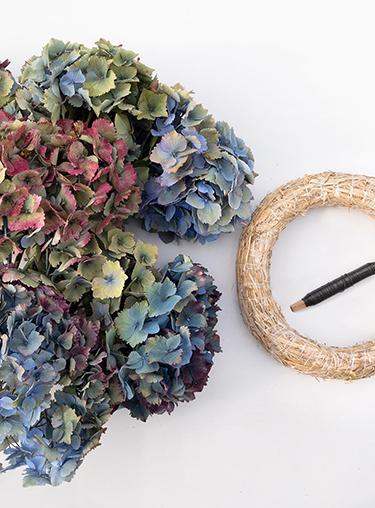 Materialien für Hortensienkranz auf weißem Hintergrund