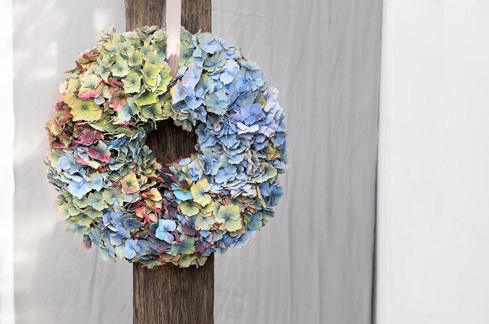 Fertiger Hortensienkranz an Holzlatte aufgehängt