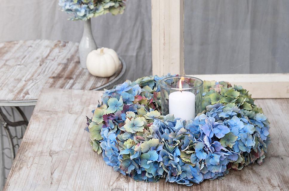 Bunter Hortensienkranz mit Windlicht auf Holztisch