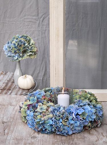Bunter Herbstkranz aus Hortensien mit Windlicht und Baby Boo Kürbis auf Holztisch
